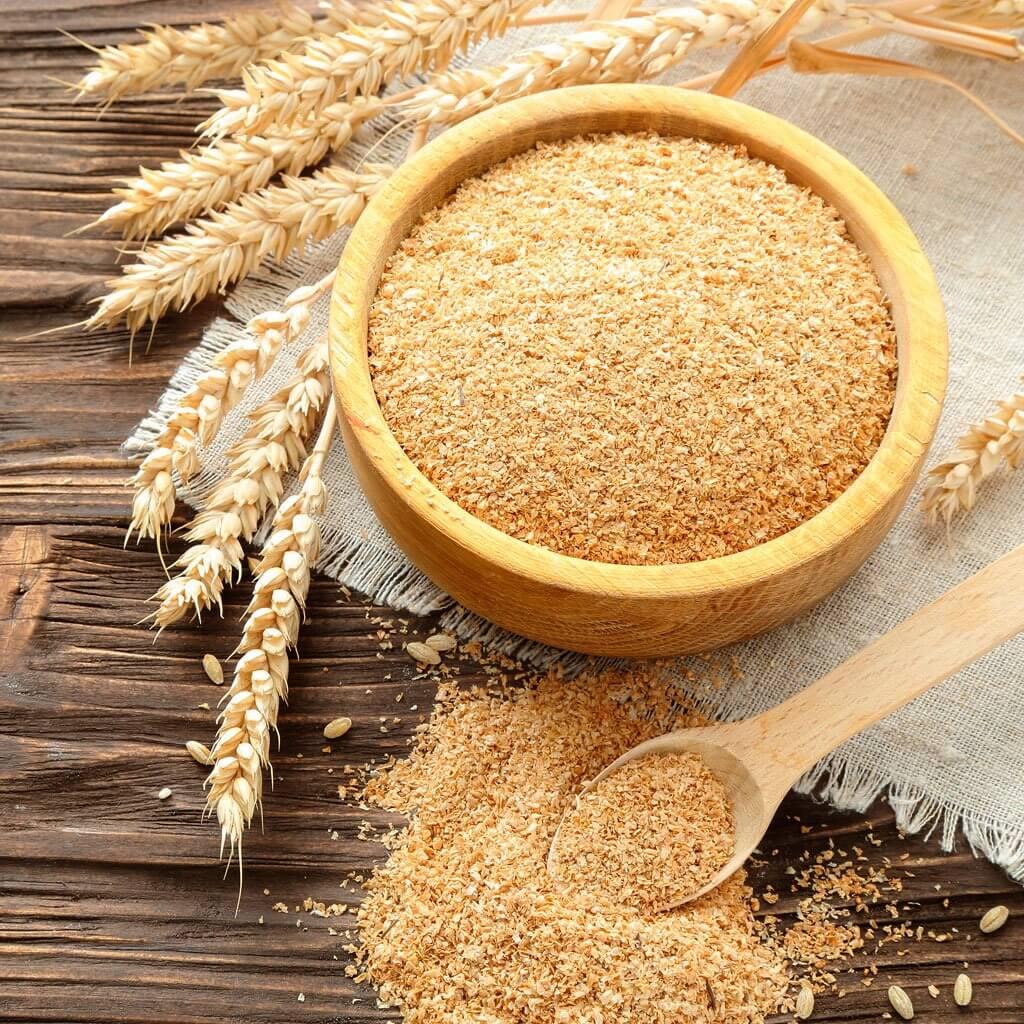 Salvado trigo en bol sobre mesa madera